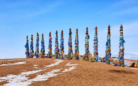 Thirteen sarge are ritual pillars in Buryat culture. Wooden poles with a lot of imposed multicolored flaps and ribbons made of fabric. Cape Burkhan. Olkhon Island. Irkutsk region. Russia