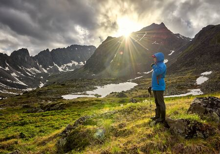 Pass hopping. Woman stands on mound in mountain tundra on cold morning. The sun's rays beautifully illuminate space next to girl