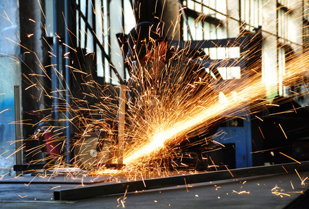 Metal works. Electric wheel grinding on steel structure in factory Фото со стока