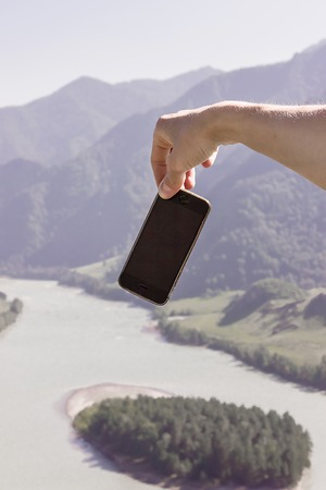 Cell phone in hand against the mountain landscape