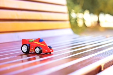 Toy childrens small car left on the bench
