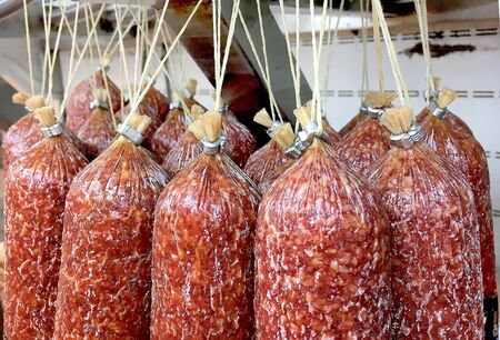 a lot of sticks of smoked sausage hanging in the store on display