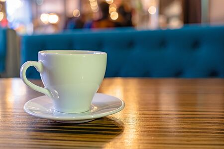 A white Cup of tea on a wooden table in a cafe close-up. Blurred background and with space for text.