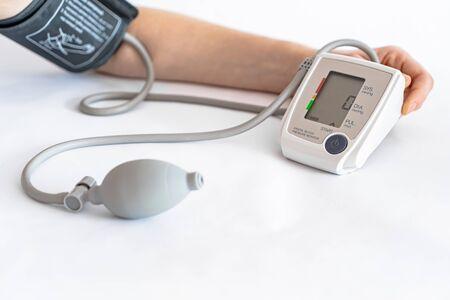 Mesure de la pression artérielle avec un appareil électronique sur fond blanc en gros plan. Banque d'images