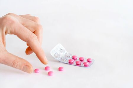 To take the pill, take the pain meds. Tablets in hand on a white background close-up and blurred focus. Foto de archivo