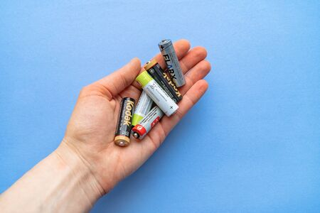 Old used batteries in hand on a blue background.