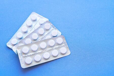 Aspirin in a blister on top. Vitamin C pills in a pack. White tablets in a blister on a blue background close-up with soft focus. Space for text. Zdjęcie Seryjne