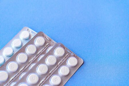 Aspirin in a blister on top. Vitamin C pills in a pack. White tablets in a blister on a blue background close-up with soft focus. Space for text.