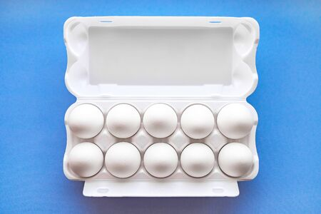 White eggs in a package on a blue background close-up view from above. Soft focus.