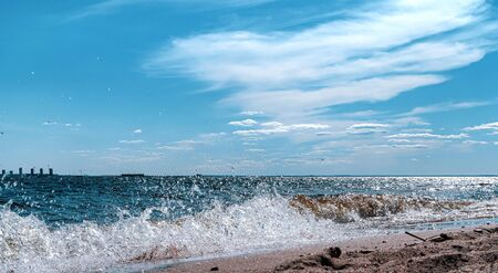 Seascape. Sandy beach on the sea on a Sunny day with beautiful clouds. 免版税图像