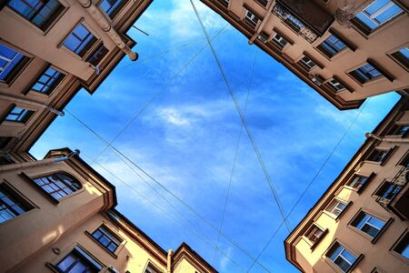 Courtyards of wells in St. Petersburg, a view from below of the blue sky without clouds.