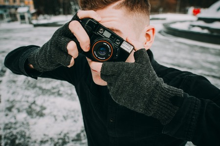 portrait of stylish handsome man with camera. Taking photo