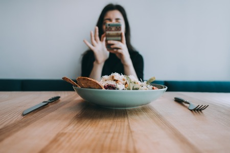 Woman taking food photo on smartphone camera before having the meal
