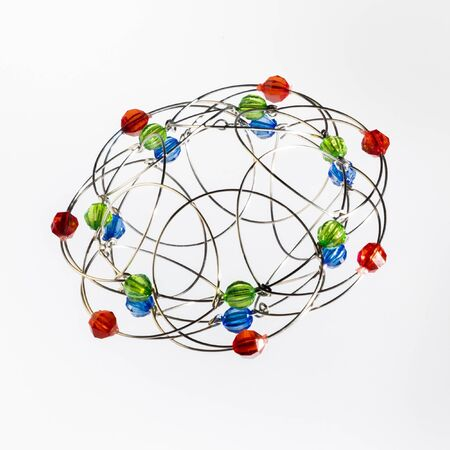 Wielokolorowy, ręcznie robiony trójwymiarowy model geometrycznej bryły na białym tle.