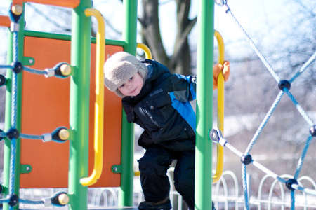 Beautiful boy playing  on the playground  in winter park. Full length portrait photo