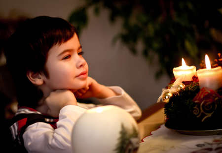 christmastide: handsome boy sitting in front of candles on Christmas Eve. Christmas. New Year. Stock Photo
