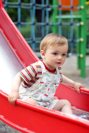 Cute little boy  come down from the children`s slide. Summer photo
