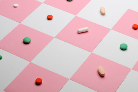 Tablets and pills on a chessboard of stickers. Free space