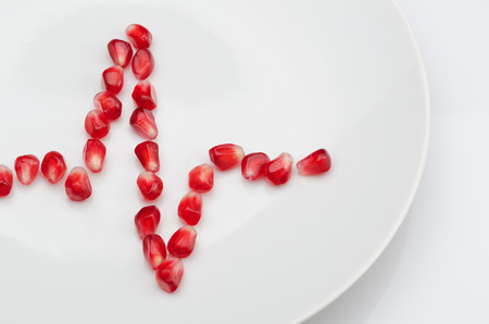 Cardiogram from pomegranate seeds on the white plate. The concept of a healthy diet