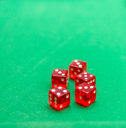 playing five red dice on a green background Stock Photo