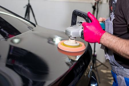 Ein Mann poliert ein schwarzes Auto mit einer Poliermaschine Standard-Bild - 77230160