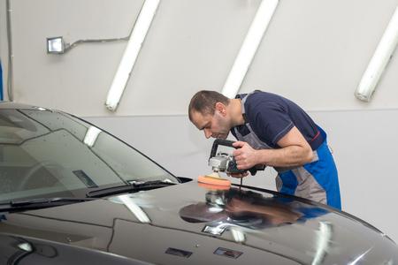 Een man polijst een zwarte auto met een polijstmachine