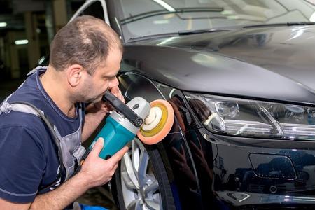 Un hombre pulida un coche negro con una máquina de pulir Foto de archivo - 80676131