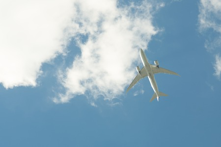 Airplane flying against the blue sky Stock Photo