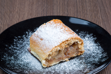 bakery products: Slice of apple strudel on a black plate