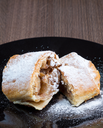 bakery products: Two pieces of apple strudel on a black plate