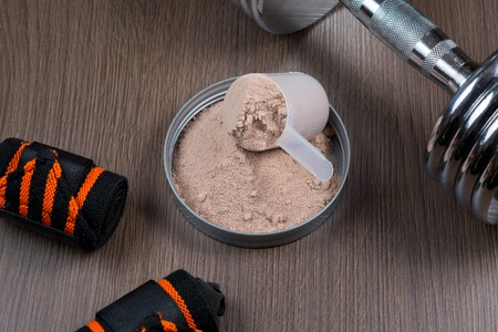 Whey protein in a measuring bucket with a metal dumbbell on a wooden background Stock Photo