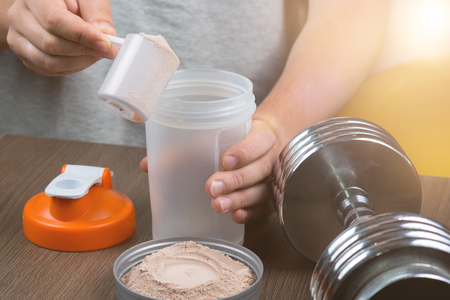 Sports, fitness, man preparing a protein shake in a shaker