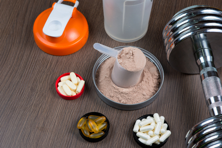 Whey protein in a measuring bucket with a metal dumbbell and shaker on a wooden background