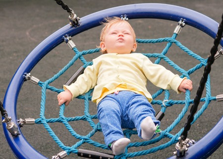 A baby kid is riding on a swing in the autumn in the park Stock Photo
