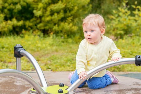 playground rides: A baby boy rides on a carousel in the playground