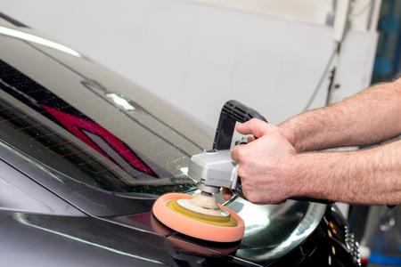 A man polishes a black car with a polisher 版權商用圖片