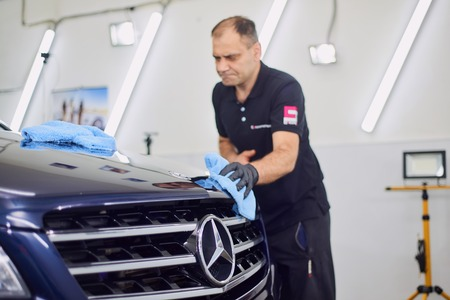 Moscow. Russia. May 30, 2018. A man polishes a blue Mercedes car ml. Foto de archivo - 104748796