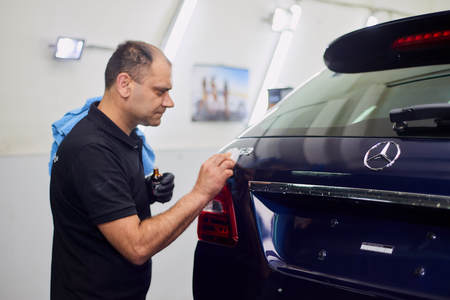 Moscow. Russia. May 30, 2018. A man polishes a blue Mercedes car ml. Foto de archivo - 104748800