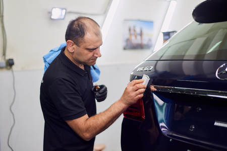Moscow. Russia. May 30, 2018. A man polishes a blue Mercedes car ml. Foto de archivo - 104748801
