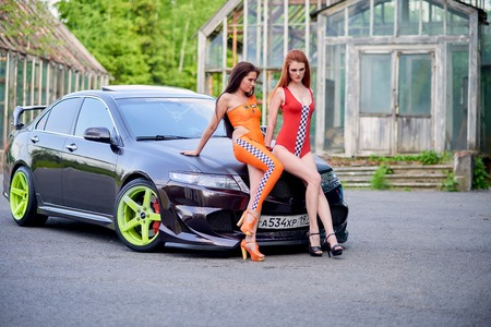 Moscow. Russia. May 26, 2015. Two beautiful girls next to a racing, sports car. Foto de archivo - 104748884