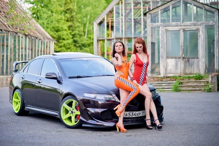 Moscow. Russia. May 26, 2015. Two beautiful girls next to a racing, sports car. Foto de archivo - 104748886