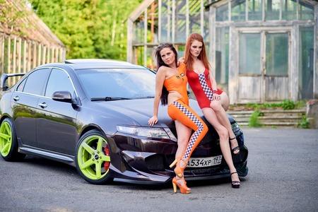 Moscow. Russia. May 26, 2015. Two beautiful girls next to a racing, sports car. Foto de archivo - 104748889