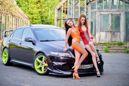Moscow. Russia. May 26, 2015. Two beautiful girls next to a racing, sports car. Foto de archivo - 104748890