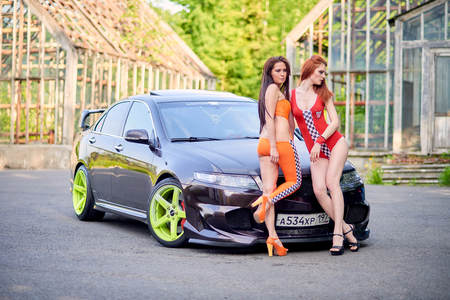 Moscow. Russia. May 26, 2015. Two beautiful girls next to a racing, sports car. Foto de archivo - 104748893