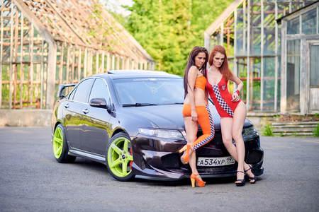 Moscow. Russia. May 26, 2015. Two beautiful girls next to a racing, sports car. Foto de archivo - 104748896