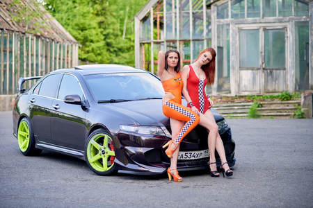 Moscow. Russia. May 26, 2015. Two beautiful girls next to a racing, sports car. Foto de archivo - 104748902