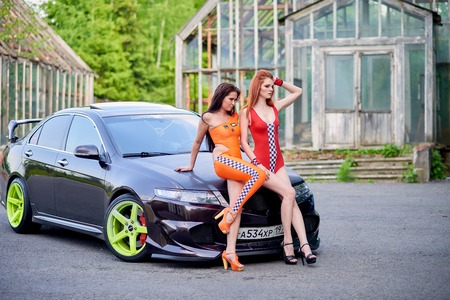 Moscow. Russia. May 26, 2015. Two beautiful girls next to a racing, sports car. Foto de archivo - 104748906