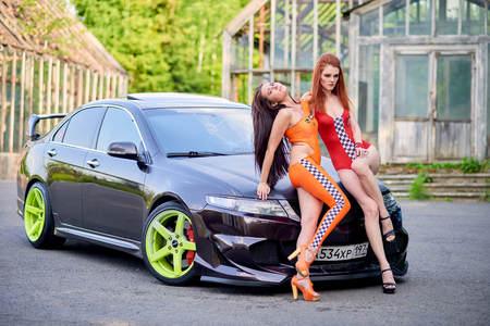 Moscow. Russia. May 26, 2015. Two beautiful girls next to a racing, sports car. Foto de archivo - 104748907