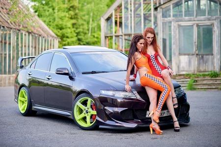 Moscow. Russia. May 26, 2015. Two beautiful girls next to a racing, sports car. Foto de archivo - 104748908