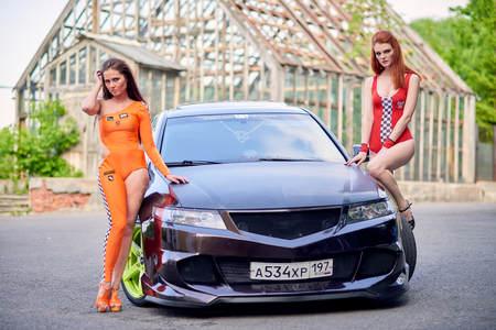 Moscow. Russia. May 26, 2015. Two beautiful girls next to a racing, sports car. Foto de archivo - 104748910